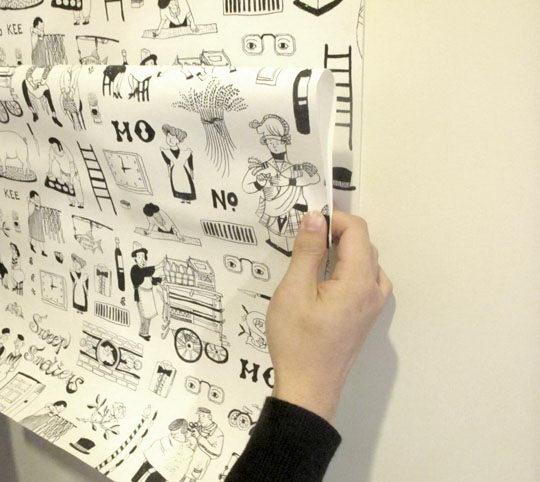 一边贴一边顺着把折起来的墙纸往下拉。